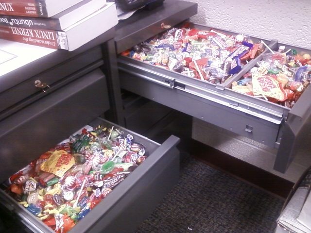 An office desk with two drawers opened. Each drawer is filled to the top with individually wrapped pieces of candy. The image exists for comic value.